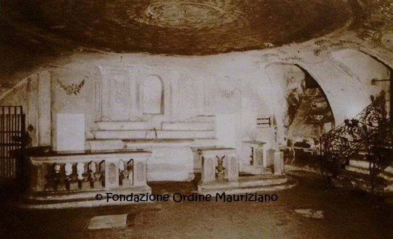 L'altare della cappella e, a destra, l'ingresso alla cripta da Via della Basilica (non più esistenti) prima del 1985. Immagine tratta dal volume: Lo Faso - Scordo - Reviglio, La Basilica Mauriziana, Roberto Chiaramonte Editore